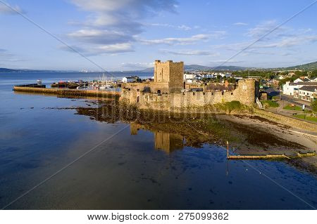 Medieval Norman Castle In Carrickfergus Near Belfast In Sunrise Light. Aerial View With Marina, Yach