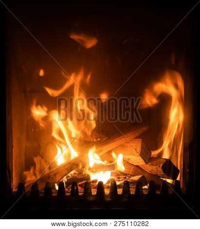 Firewood burning in stove, logs engulfed in flames, detail interior scene, winter cosyness concept poster