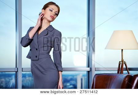 Business woman in an office environment with large stained-glass window on background