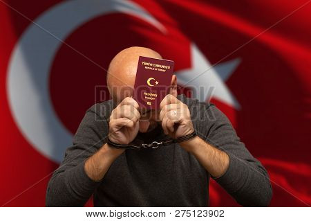 Turkish citizen detained in handcuffs with passport in hand poster