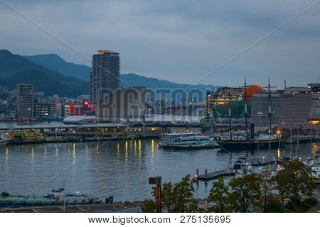 Nagasaki, Japan - October 23, 2018: Nagasaki port with ferries and cruiseboats surrounded by mountains at twilight