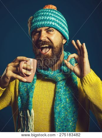 Happy Man In Sweater And Scarf Holds Cup Of Hot Tea Showing Ok Gesture. Cool Manly Stylish Fashionab
