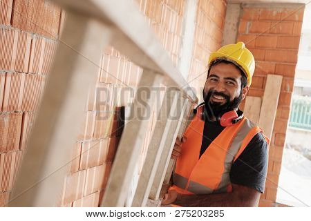 Portrait Of Happy Hispanic Worker Smiling In Construction Site