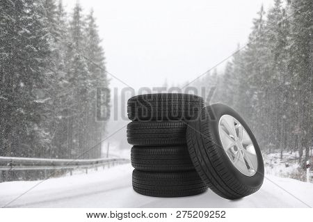 Set Of Winter Tires On Forest Highway During Snowfall. Car Service