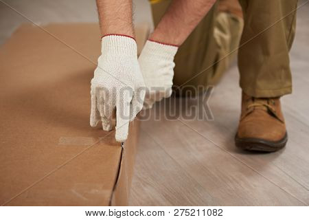 Unpacking Box Concept. Man In Gloves Unpacking Box With Knife