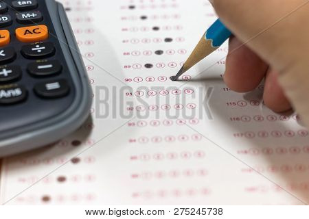 Dry Hand Of Mature Student Doing Exams By Using Pencil Selected Multiple Choice On Standardized Test