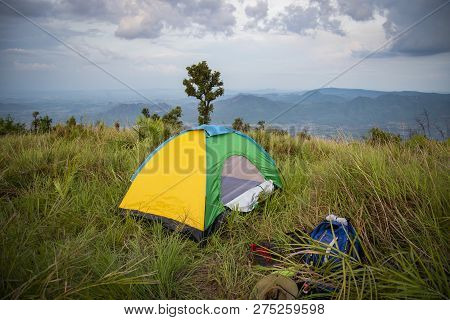 tent areas on hill sunset / colorful hiking camping tent on grass green field and packing backpack on the mountain - landscape area camping tents yellow in the wild with cloud sky on summer day