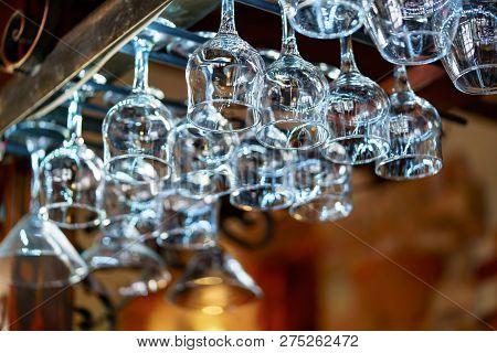 Glasses Hanging Over Bar Rack. Empty Glasses For Wine Above A Bar Rack