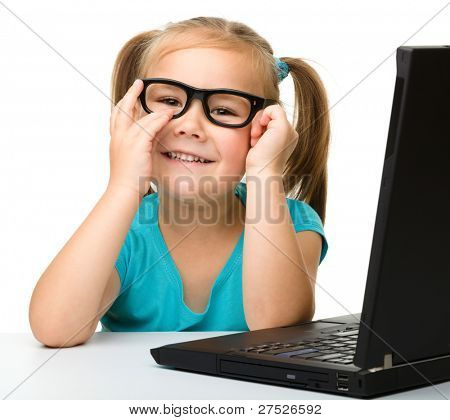 Cute little girl is sitting at table with her black laptop and wearing glasses, isolated over white