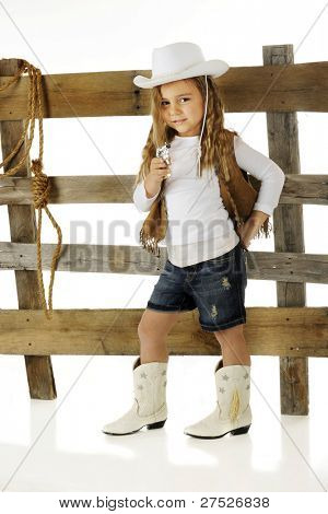 """A cute kindergarten """"Cowgirl"""" in front of a rustic rail fence as she prepares to shoot her cap gun.  On a white background."""