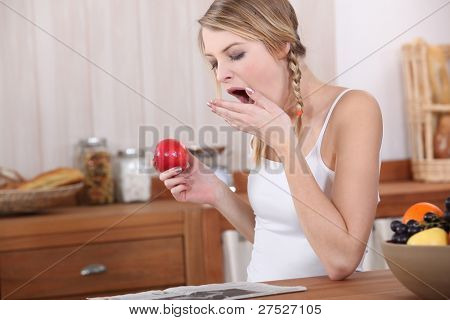 Young woman yawning over breakfast