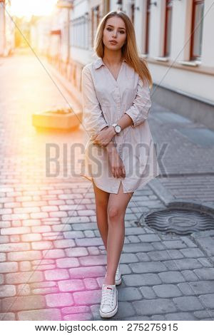 Hipster Young Woman In A Trendy Summer Pink Dress In White Sneakers Is Standing On An Old Street In
