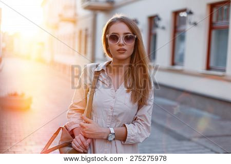 Stylish Young Hipster Woman In Stylish Sunglasses In A Trendy White Dress With A Fashionable Brown L