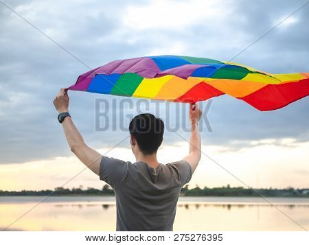Young Man Holding A Rainbow Flag Over His Head Beside The Lake On Sunset Sky Background. Lgbt, Gay,