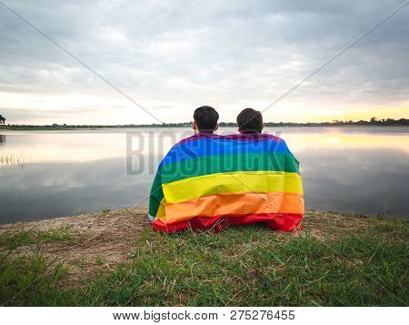 Two Young Man Covered By A Rainbow Flag  Beside The Lake On Sunset Sky Background. Lgbt, Gay, Pride