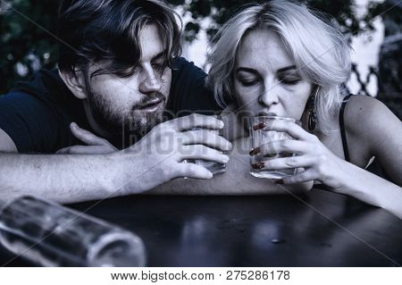 Alco Addiction Concept. Depressed And Hopeless Couple Sitting After Using Drunk Alcohol On The Stree