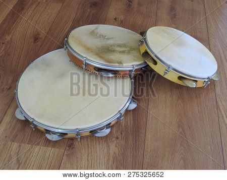 Close-up Of Three Pandeiros  (tambourines), A Brazilian Musical Percussion Instrument, On A Wooden S