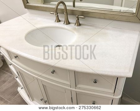Bathroom vanity cabinet with marble counter tops. Image to be used as magazine bathroom. Marble counter in old bathroom sink, bathroom faucet, bathroom vanity, bathroom mirror, door, brush. Floor tile bathroom concept