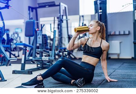 Fitness Woman Drinking Water While Sitting And Resting On The Floor In Gym. Woman Exercise Workout I