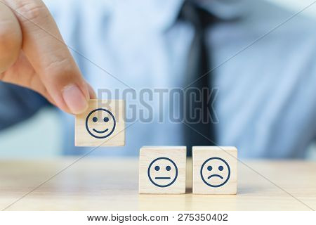 Hand Of A Businessman Chooses A Smiley Face On Wood Block Cube, The Best Excellent Business Services