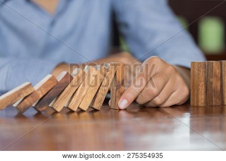 Businessman Hand Stopping Falling Wooden Dominoes Effect From Continuous Toppled Or Risk, Strategy A