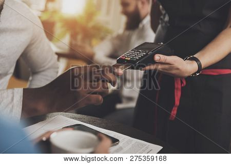 Young African American Is Calculated Credit Card. Close-up Of A Afro-american Man Paying For An Orde