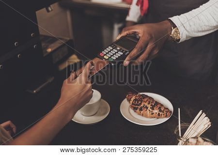 Young Girl Is Calculated The Cafe By Credit Card. Smiling Afro American Barista Man Unwrapping A Bea