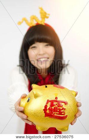 A Asian Girl Hold a Golden Piggy bank