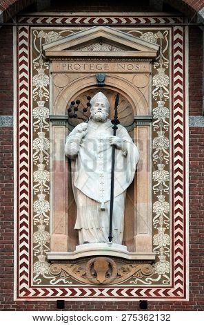 MILAN, ITALY - JUNE 22, 2018: Statue of Sant'Ambrogio (Saint Ambrose) patron of the city of Milan. Detail of the clock tower of the Sforza Castle XV century (Castello Sforzesco). Lombardy, Italy