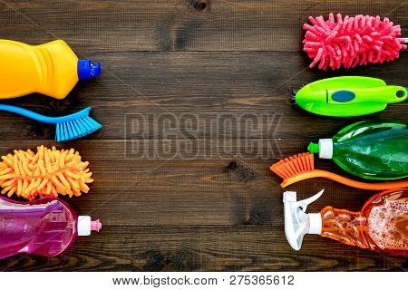 Housecleaning With Detergents, Soap, Cleaners And Brush In Plastic Bottles On Wooden Background Top