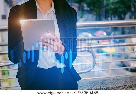 Young Asian Investor Business Woman Using Mobile Tablet With Graphic Candle Stick Graph Chart Of Sto