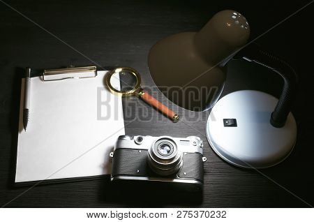 Blank Page, Pen, Film Photo Camera, Magnifying Glass And Lamp On A Black Detective Agent Table Backg
