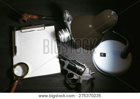 Blank Page, Pen, Film Photo Camera, Magnifying Glass, Handgun And Smoking Pipe On A Black Detective