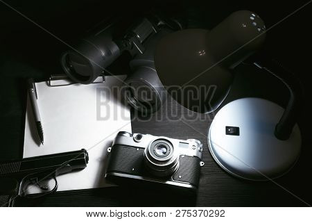 Blank Page, Pen, Film Photo Camera, Handgun And A Binoculars On A Black Detective Agent Table Backgr