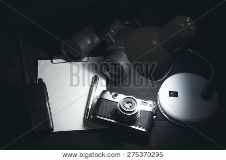 Blank Page With Copy Space, Pen, Portable Radio, Binoculars And Photo Camera On A Black Spy Agent Ta