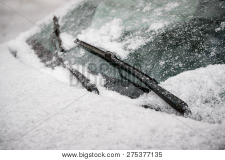 Car wiper blades clean snow from car windows. Flakes of snow covered the car with a thick layer. Safe driving with working wipers and clean windshield. poster