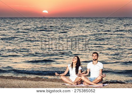 Young Man And Woman Do Yoga And Meditate On The Beach At Dawn. Healthy Lifestyle Concept