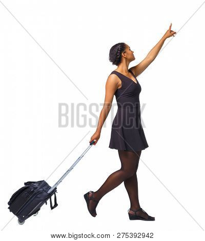 Back view of a black African-American walking with a suitcase and pointing hand forward.  backside view of person.  Rear view people collection. Isolated over white background. A young girl is looking
