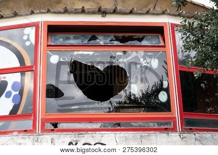 Vandalism Concept. Building With Broken Window And Graffiti. Vandal Graffiti On The Window Of A Hous