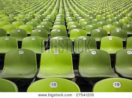 bleachers at stadium, endless rows of green plastic seats