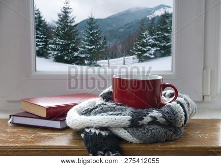 Winter Background - Cup With Candy Cane, Woolen Scarf And Gloves On Windowsill And Winter Scene Outd