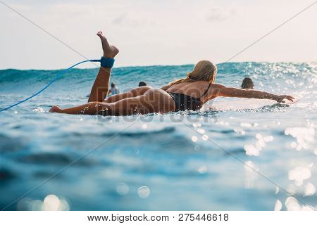 June 22, 2018. Bali, Indonesia. Surf Girl Floating On Surfboard. Woman In Ocean During Surfing.