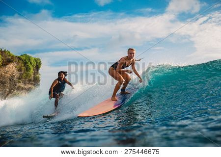 June 22, 2018. Bali, Indonesia. Surf Girl Ride On Surfboard. Surfers In Ocean During Surfing.