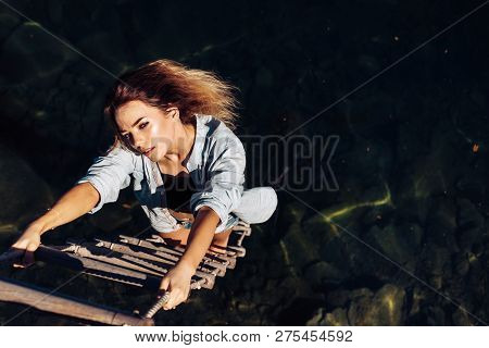 Ambition Wings Her Spirit. Sexy Woman Climbing Up Rope Ladder. Sensual Woman Hang On Rope Over Water