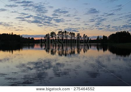 Silhouettes Of Trees And Colorful Sky Are Reflected In The Forest Lake In The Evening. Unusual And P