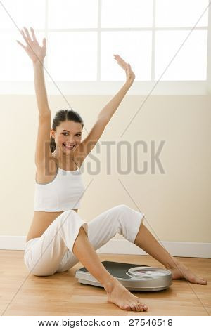 Happy young woman with weight scale