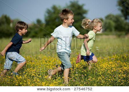 Three cute children running outdoors