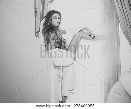 Girl In Black Lingerie Enjoys Morning Near Window. Sexy Nude Woman With Long Hair Raises Leg High. L