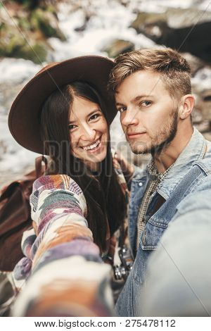 Happy Hipster Couple Making Selfie And Smiling At Waterfall In Forest Mountains. Stylish Couple In L