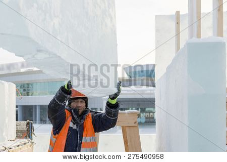 Sling fitter in a jacket and helmet unloads ice blocks poster